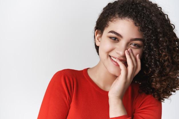 Schattige tedere romantische jonge spaanse aantrekkelijk meisje grinniken kokette dekking glimlach palm grijnzend veel plezier flirten brutaal kijken camera staand geamuseerd vermaakt witte muur