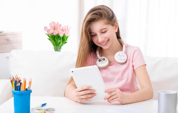 Schattige tiener bladert door interessante artikelen op internet op haar persoonlijke tablet