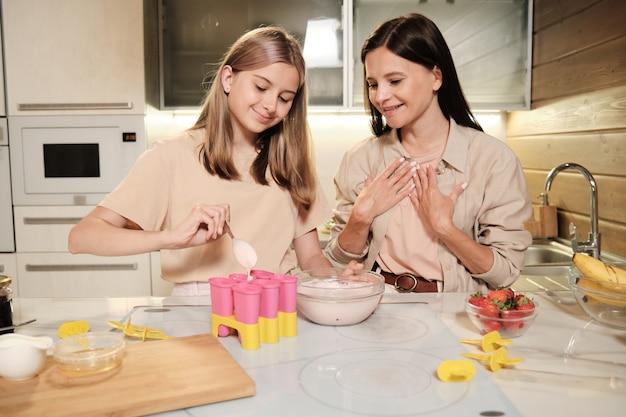 Schattige tiener blond meisje vloeibaar zelfgemaakt ijs in groep siliconen vormen zetten terwijl haar opgewonden moeder in de buurt staan