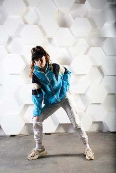 Schattige tiener hiphop dansen in reflecterende broek, in een studio met neonverlichting. dans kleur poster.