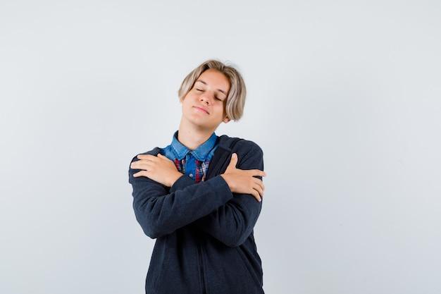 Schattige tienerjongen die zichzelf omhelst, zijn ogen gesloten houdt in shirt, hoodie en er ontspannen uitziet, vooraanzicht.
