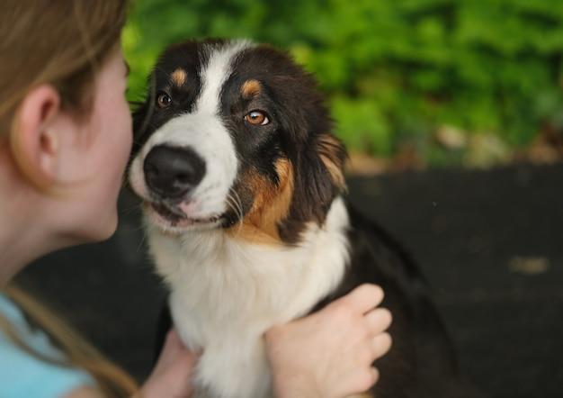 Schattige tienermeisje kus omarmen australische herder drie kleuren puppy hondje in zomer park