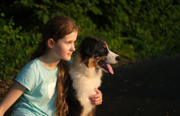 Schattige tienermeisje omhelst australische herder drie kleuren puppy hondje in de zomer