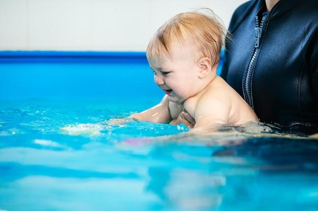 Schattige trieste babyjongen die leert zwemmen in een speciaal zwembad voor kleine kinderen