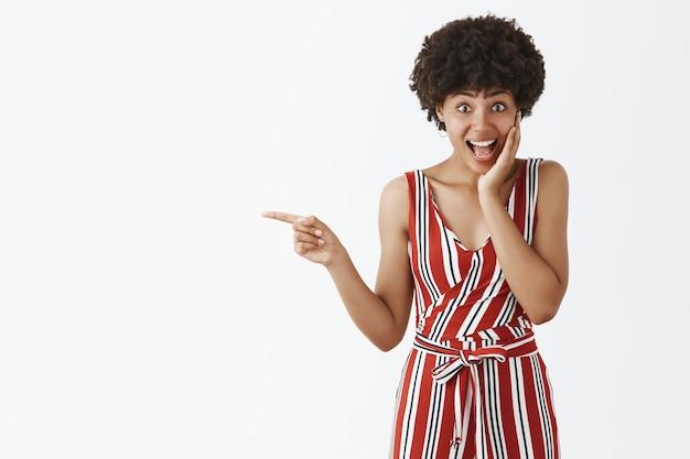 Schattige verbaasd en onder de indruk aantrekkelijke afro-amerikaanse vrouwelijke vrouw in stijlvolle formele gestreepte overall wang aanraken van verbazing en naar links wijzend met wijsvinger glimlachend van verbazing