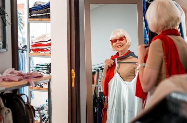 Schattige verschijning. blij modieuze grijsharige vrouw die in het winkelen spiegel door rode zonnebril kijkt terwijl zomerjurk voor haar houdt