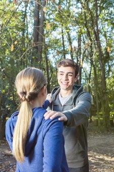 Schattige vriendje doen warm-ups met zijn vriendin in het bos