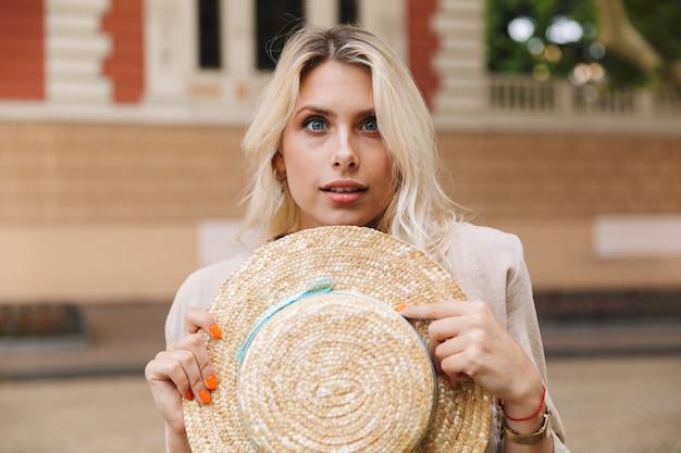 Schattige vrouw 20s met strooien hoed, tijdens het wandelen door stadsstraat