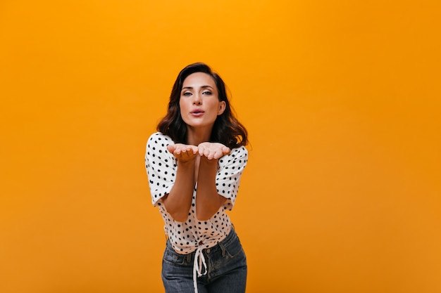Schattige vrouw blaast kus op oranje achtergrond. donkerharige dame in witte polka-dot blouse en spijkerbroek vormt voor camera.