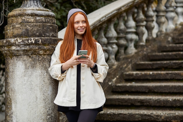 Schattige vrouw die 's ochtends op historische plaatsen loopt met behulp van smartphone volwassen vrouwelijke reiziger surfen...