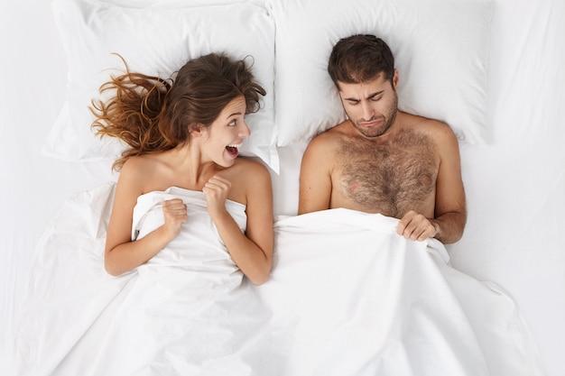 Schattige vrouw die zich opgewonden voelt, lacht en haar vuisten balde terwijl haar vriend weer seksueel kan presteren