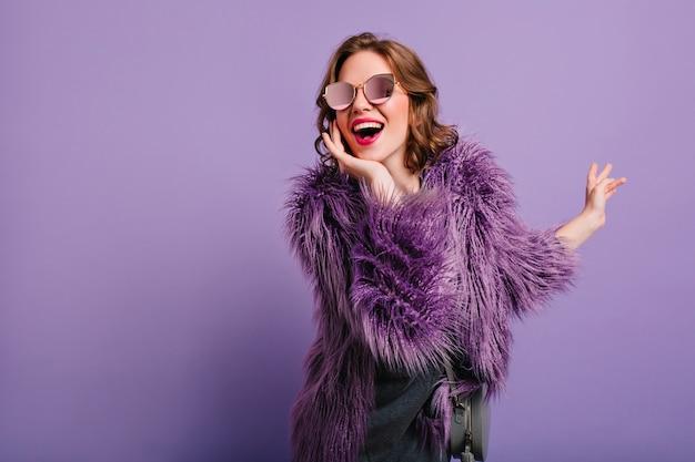 Schattige vrouw echte positieve emoties uitdrukken tijdens fotoshoot in paarse bontjas