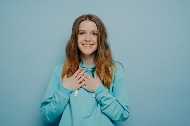 Schattige vrouw hand in hand op de borst en het uiten van geluk, opgewonden tienermeisje gekleed in vrijetijdskleding camera kijken met liefde en dankbaarheid terwijl staande geïsoleerd op blauwe studio achtergrond
