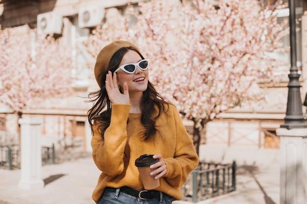 Schattige vrouw in glazen, baret zwaait met haar hand en houdt een glas koffie. leuke dame in zonnebril poseren met kopje thee tegen sakura