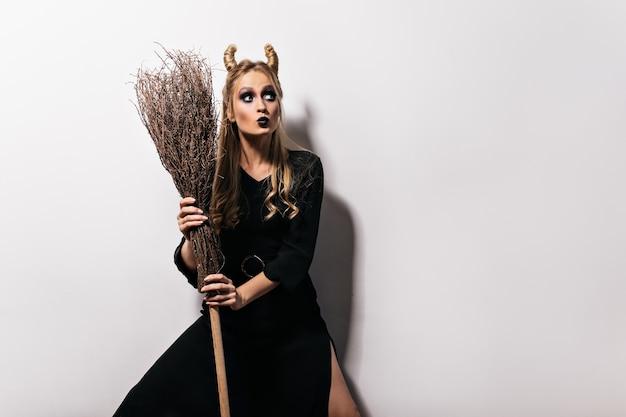 Schattige vrouw in heksenkostuum poseren op witte muur. schitterend meisje met bezem die halloween vieren.