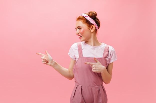 Schattige vrouw in roze jurk en witte top toont met vingers naar links op geïsoleerde achtergrond.