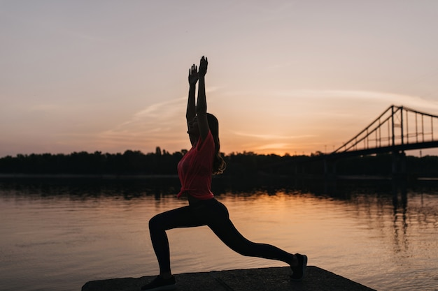 Schattige vrouw in roze t-shirt yoga doen en avondlucht kijken. outdoor portret van charmante vrouwelijke model genieten van opleiding in de buurt van de rivier.