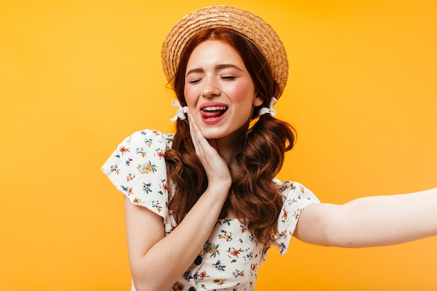 Schattige vrouw in schipper en met bogen op haar haar toont haar tong en neemt selfie op oranje achtergrond.