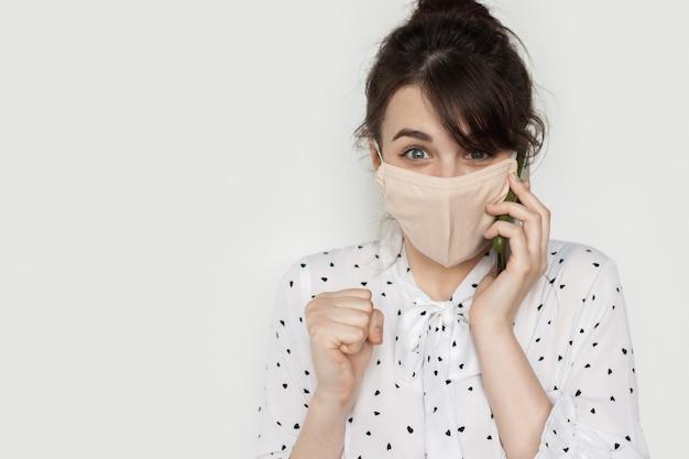 Schattige vrouw lacht naar de camera met een medisch masker en praat aan de telefoon op een witte muur met vrije ruimte
