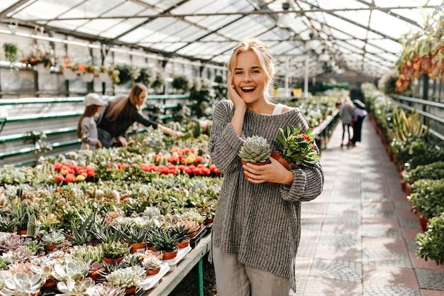 Schattige vrouw met broodje lacht oprecht en poseert met verschillende soorten cactussen en vetplanten.