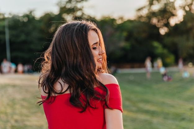Schattige vrouw met elegante kapsel poseren in park. het kaukasische donkerbruine meisje dat van jocund in een rode kleding gras bekijkt.