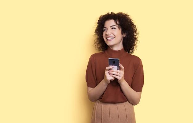 Schattige vrouw met krullend haar chatten op mobiel poseren op een gele muur met vrije ruimte