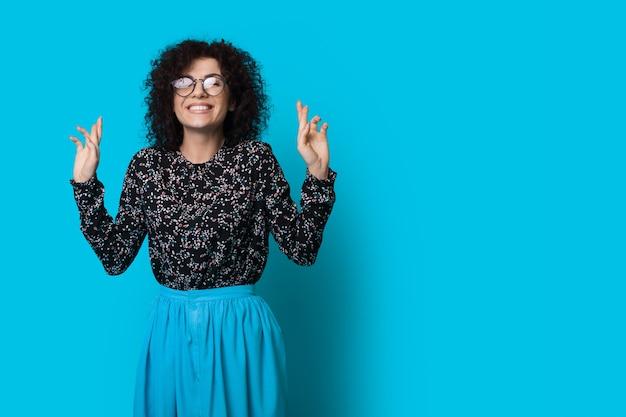 Schattige vrouw met krullend haar en bril droomt van iets met gekruiste vingers gebaren op een blauwe muur met vrije ruimte