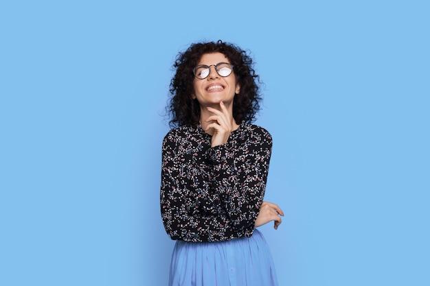 Schattige vrouw met krullend haar en bril lacht naar de camera op een blauwe studiomuur