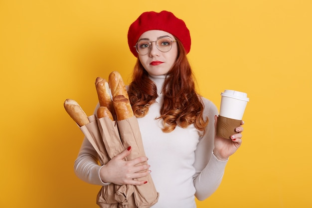 Schattige vrouw met papieren zak met vers stokbrood en koffie om mee te nemen, dame in slechte geest, met shirt, baret en bril op geel