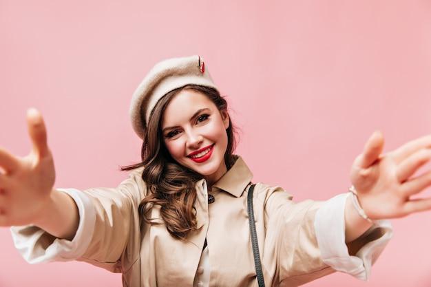 Schattige vrouw met rode lippenstift maakt selfie. portret van meisje in beige herfst outfit op roze achtergrond.