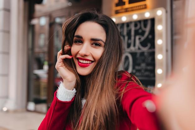 Schattige vrouw met vermoeide glimlach die foto van zichzelf op stadsruimte neemt