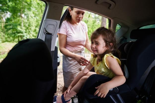 Schattige vrouwelijke baby die huilt als moeder haar op het autostoeltje zet. veiligheid van reizen in een auto met kinderen