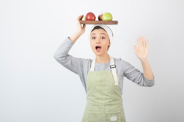 Schattige vrouwelijke kok bedrijf plaat van appels op wit.