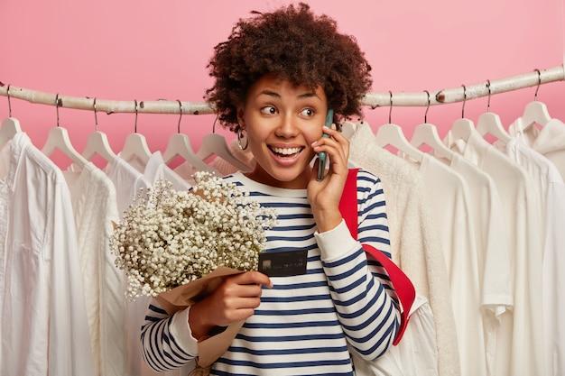 Schattige vrouwelijke shopaholic houdt creditcard, besteedt geld aan winkelen, maakt telefoongesprek, gekleed in gestreepte trui, staat tegen witte stevige kleren op hangers tegen roze achtergrond