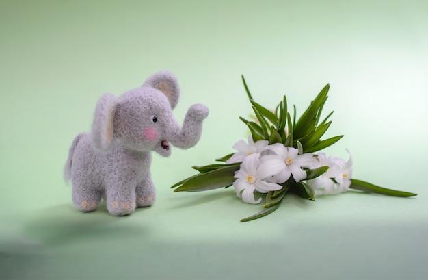 Schattige wollige speelgoedolifant met witte bloemen op een groene ondergrond