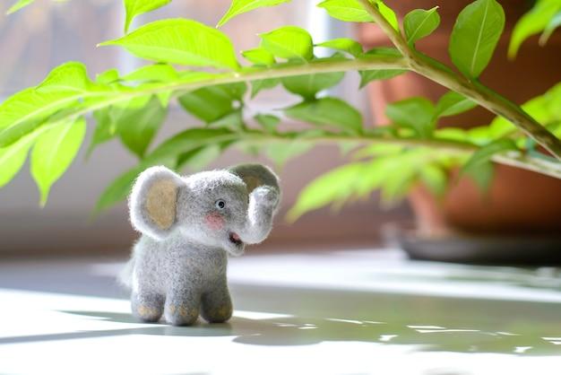 Schattige wollige speelgoedolifant onder groene bladeren op een zonnige dag
