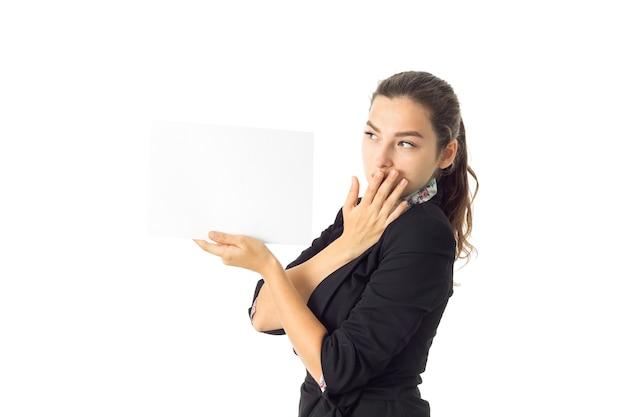 Schattige zakenvrouw in uniform met wit aanplakbiljet in handen geïsoleerd op een witte muur