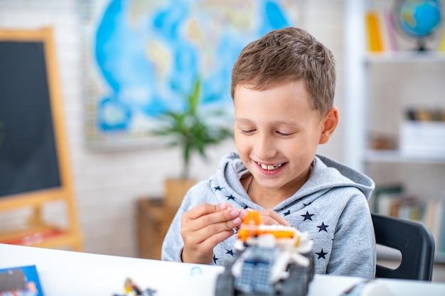 Schattige zevenjarige jongen, schooljongen, heeft plezier met constructeur, zittend aan tafel