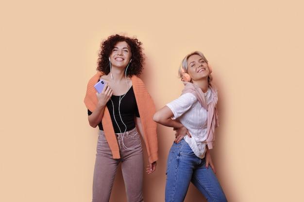 Schattige zus met krullend haar die naar muziek luistert op een gele muur met een koptelefoon