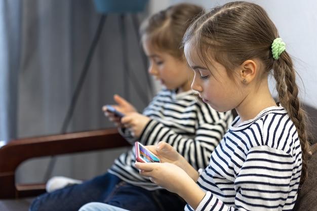 Schattige zusjes gebruiken telefoons terwijl ze thuis op de bank zitten.