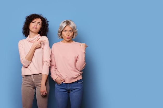 Schattige zussen in dezelfde kleren trekken grappige gezichten en wijzen naar een blauwe vrije ruimte naast hen
