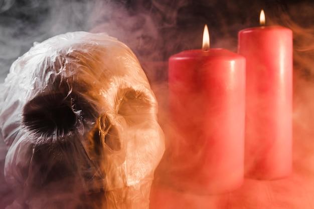 Schedel in plastic zak en kaarsen in rook
