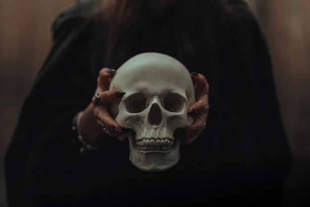 Schedel van een dode man in de handen van een heks in een zwart kostuum voor een occult satanisch ritueel
