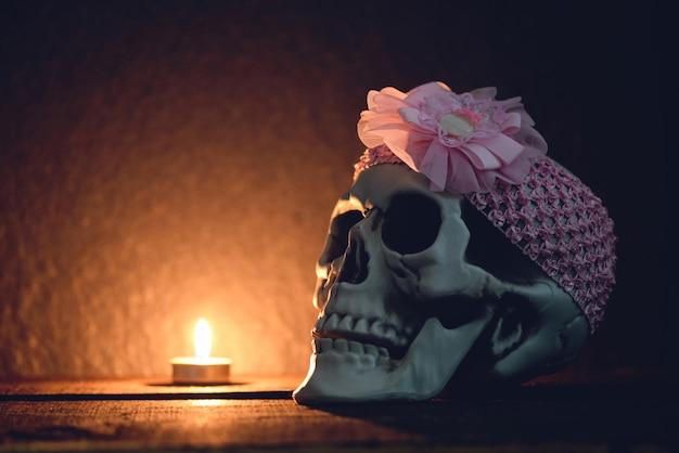 Schedelstilleven menselijke schedel met roze hoofdband rond versierd bij halloween-feestlichtkaars