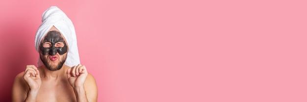 Scheel jonge man met een cosmetisch masker op zijn gezicht, met goed gesloten ogen op een roze achtergrond.