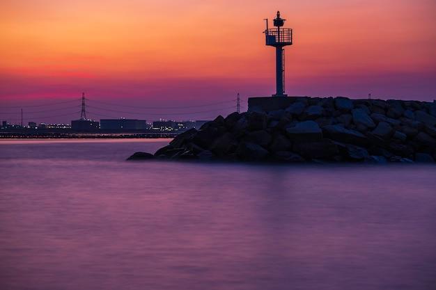 Scheepsverkeersleidingstoren in de zonsondergang van de schemertijd jetty-golfbreker om schepen te beschermen tegen zeegolven