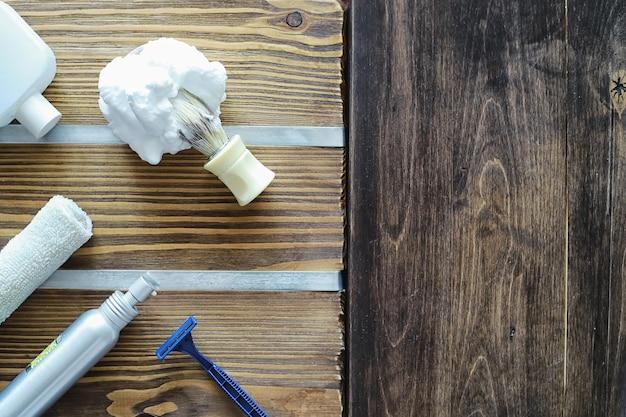 Scheeraccessoires op een houten textuurachtergrond. gereedschap. wegwerpscheermachine, borstel, schuim en gevarenscheermes.