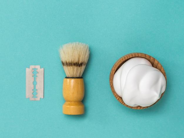 Scheerkwast en scheerschuim in een houten kom. verzorging van het gezicht van een man. plat leggen.