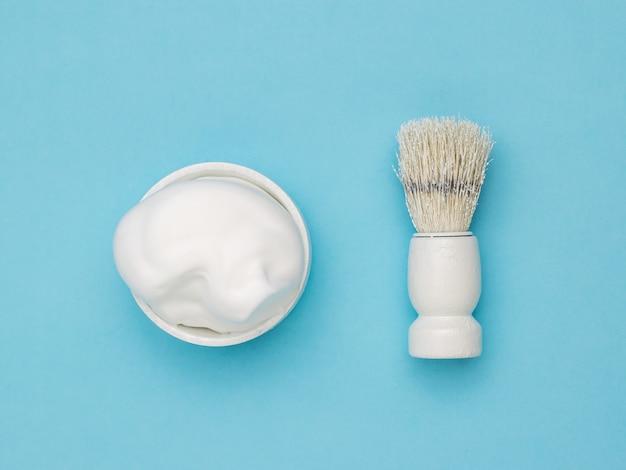 Scheerschuim in een witte kom en een witte scheerkwast op een blauwe ondergrond