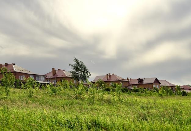 Scheidende wolken in de lucht bakstenen huizen op een rij tussen het groen